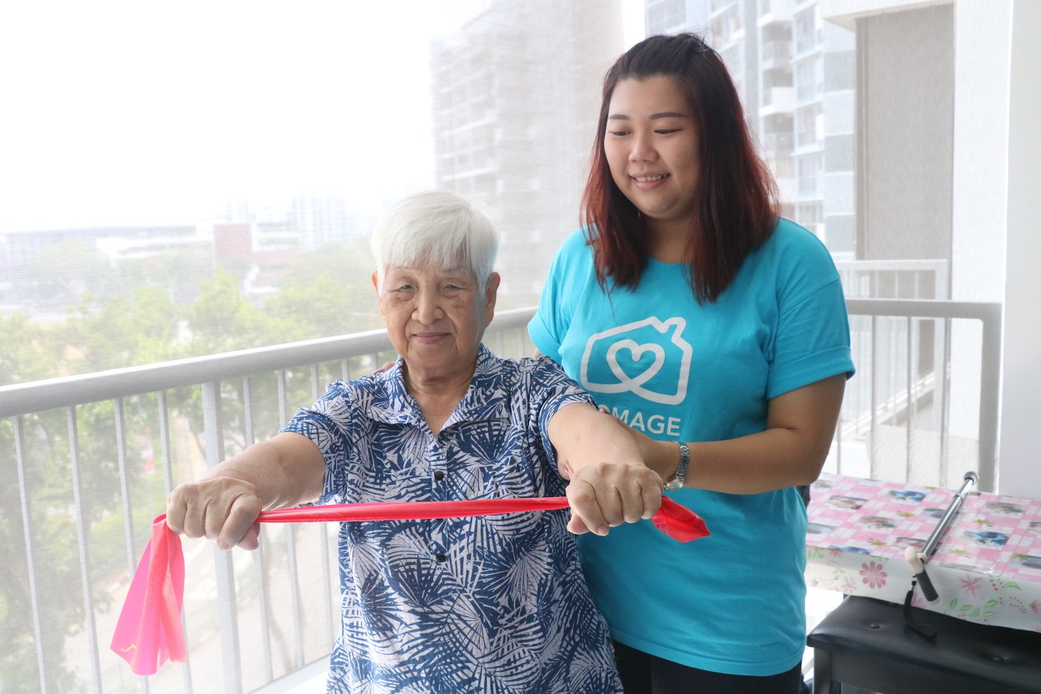 Homage Care Professional helping elderly woman to stay physically active with resistance band exercises