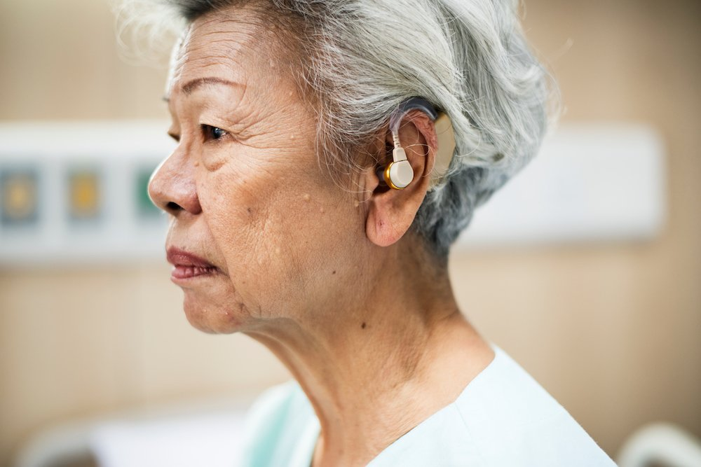 elderly asian woman wearing a hearing aid