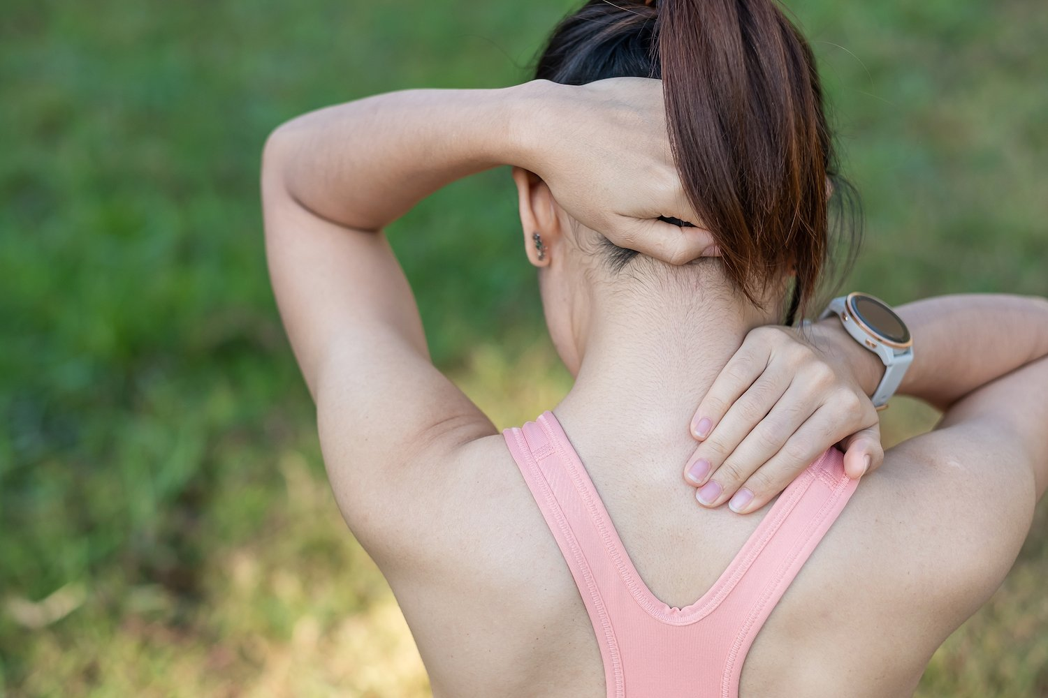 young woman holding her neck due to neck pain caused by exercise or overexertion