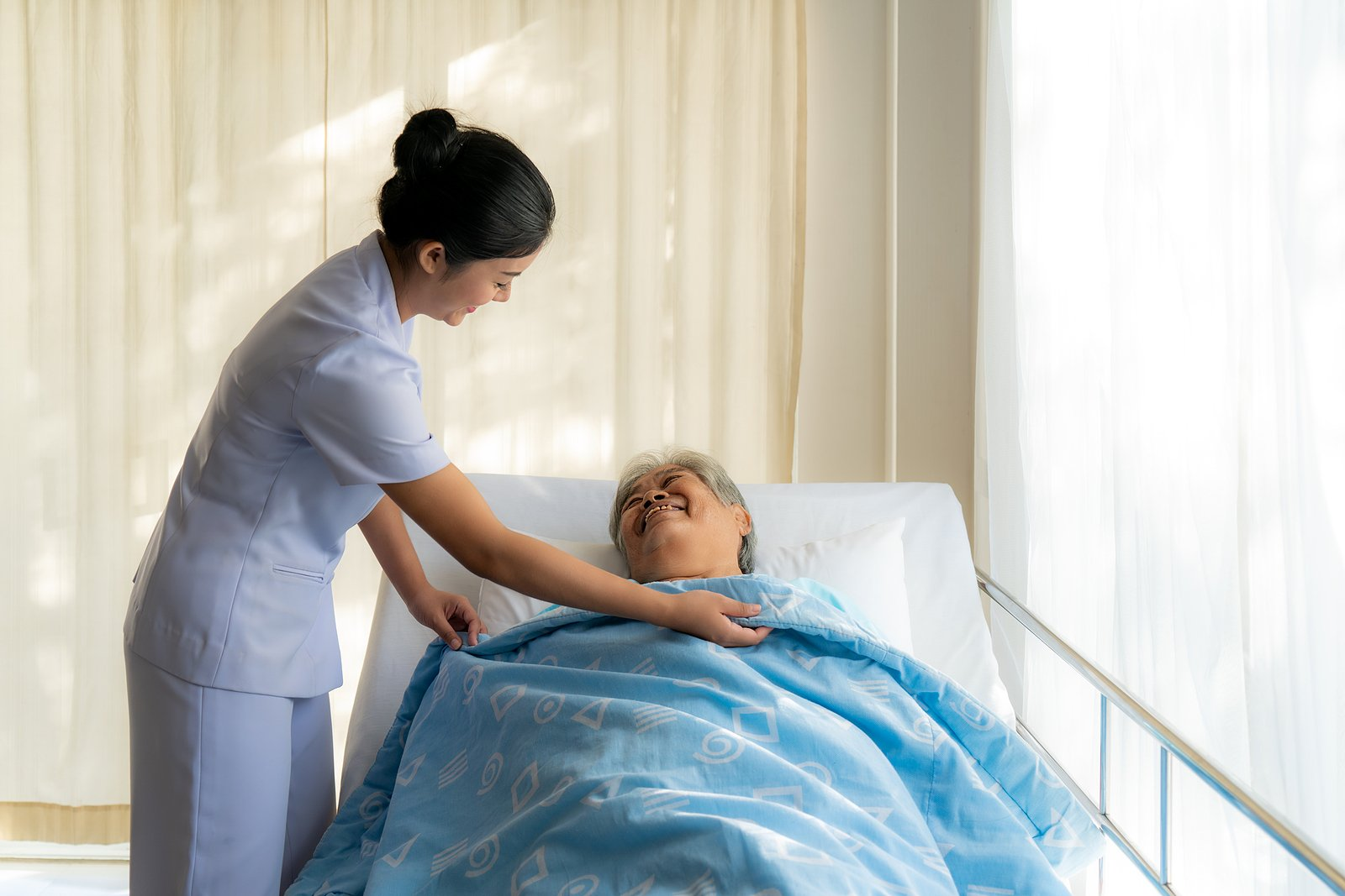 elderly woman in a hospital bed at home with a nurse
