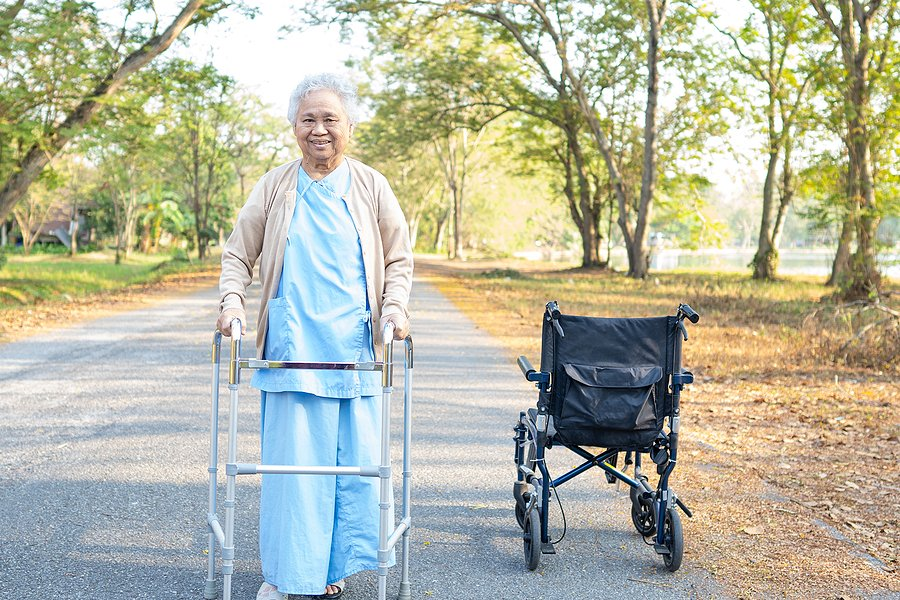 Happy elderly woman stands up from wheelchair and is walking independently using a walking frame